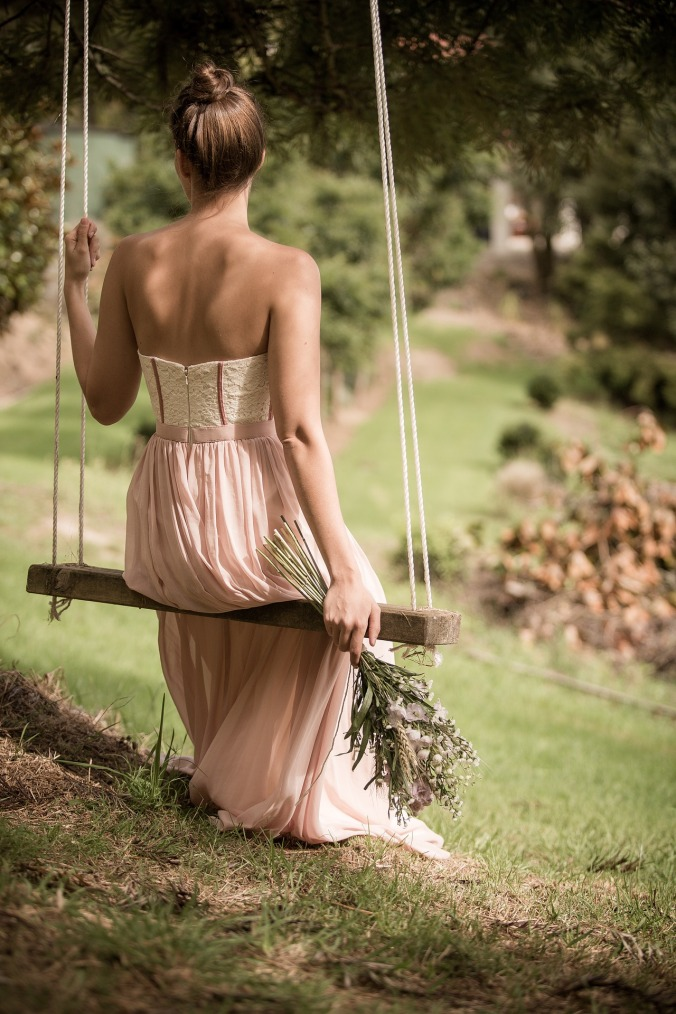 photo of woman on wooden swing