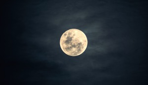 bright full moon in a dark, slightly cloudy sky
