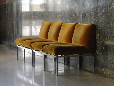 Four Brownish yellow chairs in a waiting room