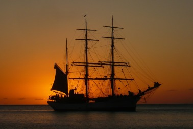 a 3 masted sailing ship at sunset