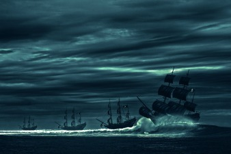 three pirate ships on a dark, cloudy ocean