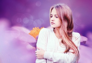 girl in white sweater in front of a purple background