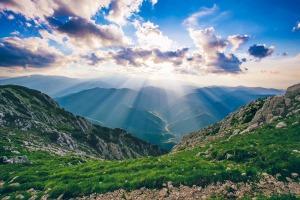 sun shining through clouds onto a green mountain range