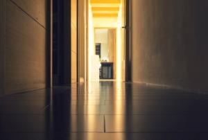 floor level view of hallway, leading to an open door