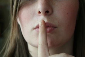 girl holding her finger to her lips as if to shush someone