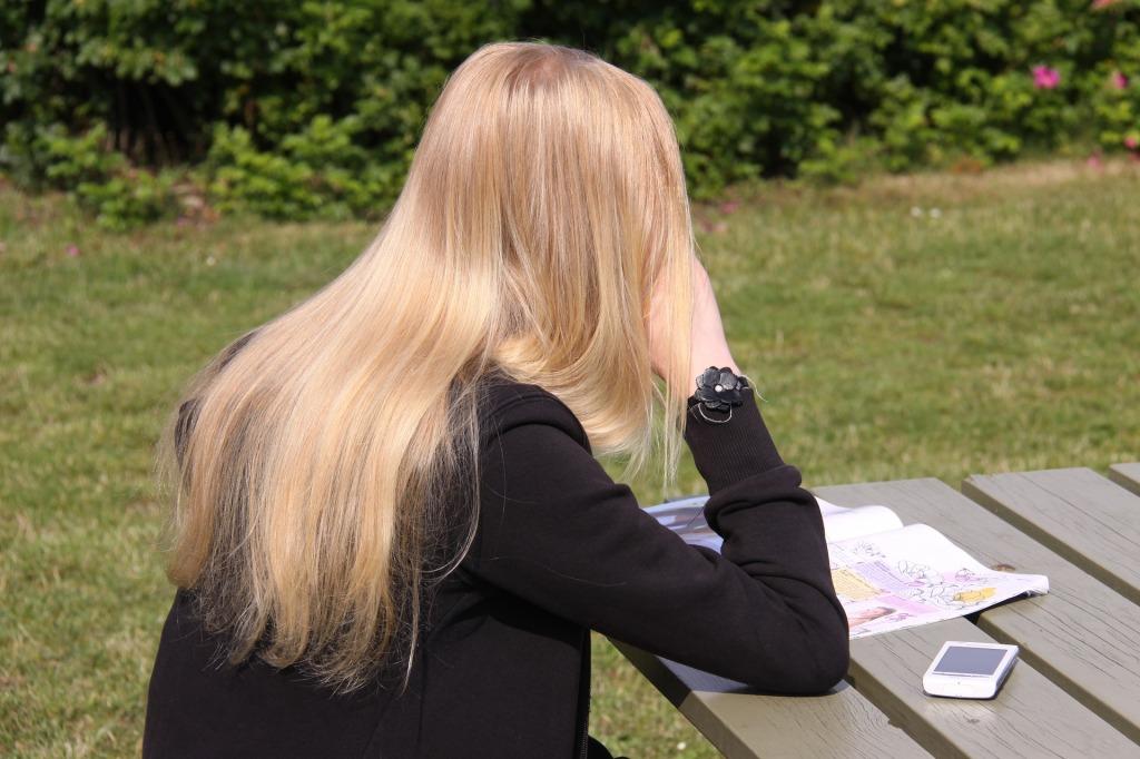 Teen girl sitting at picnic table