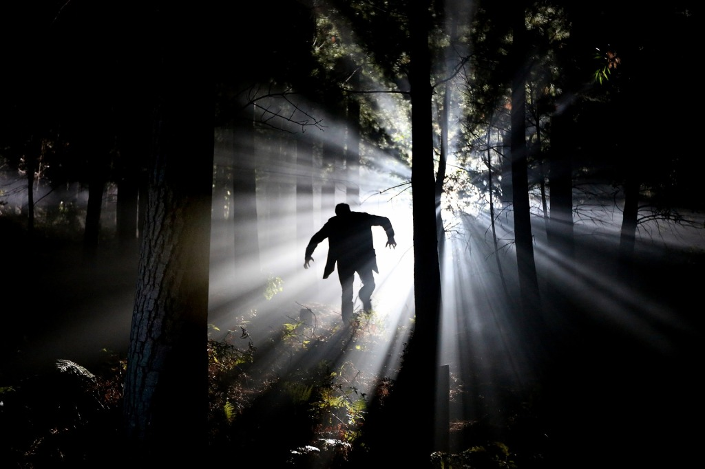 Image is an eerie photo of a man fleeing through a dark forest, backlit by streams of light.