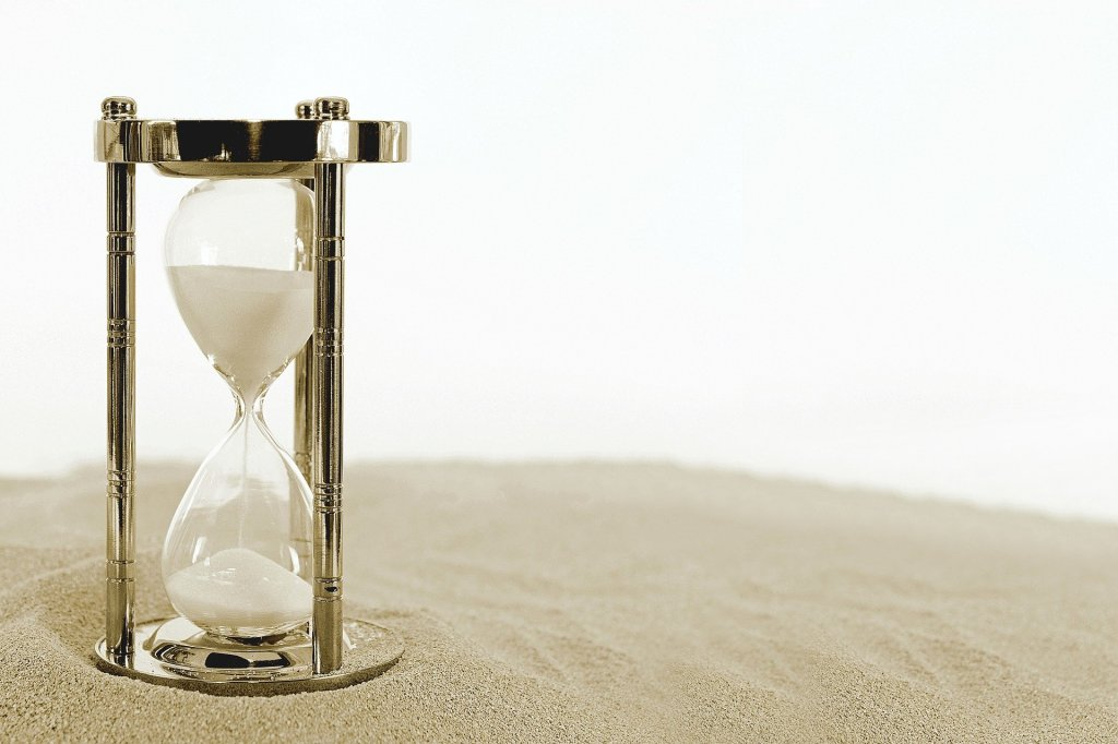 Image is of a shiny gold hourglass, with white sand trickling through, on a background of sand.