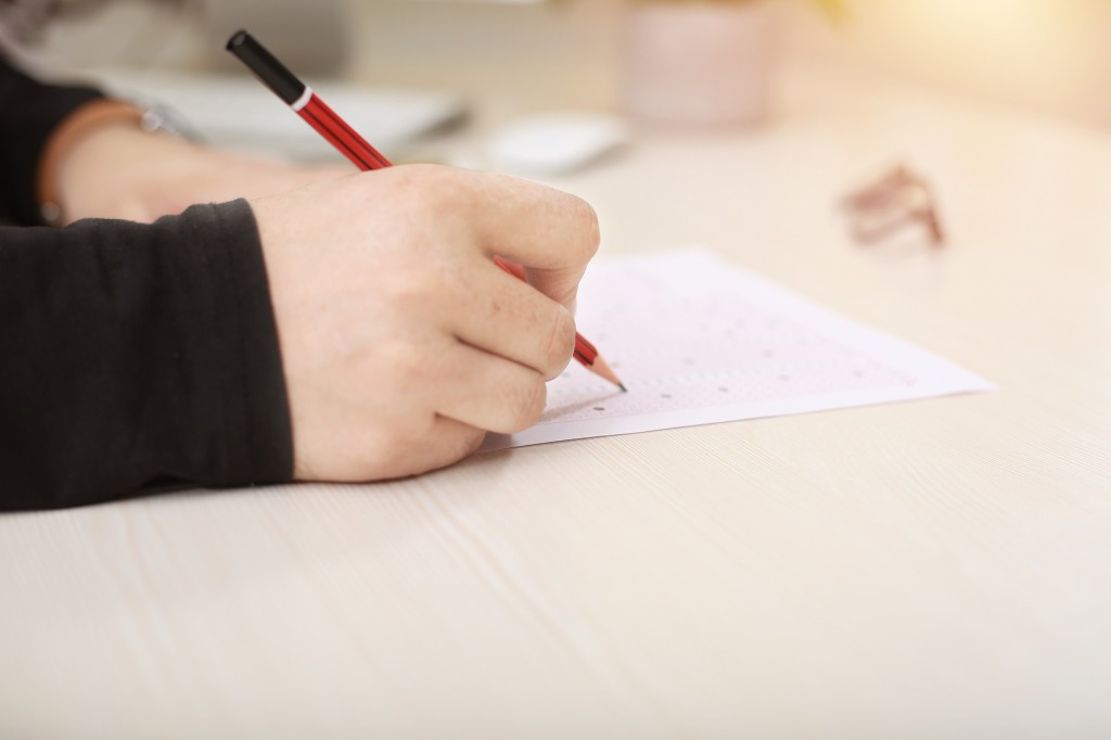 Image is of a hand holding a pencil, writing on a piece of paper.