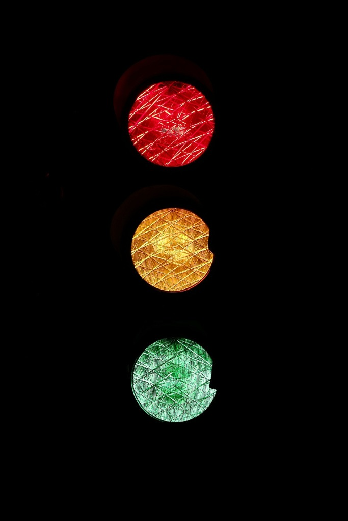 Image is of a stylized traffic signal. The three color lights (red, amber and green) are pictured floating amidst a black background.